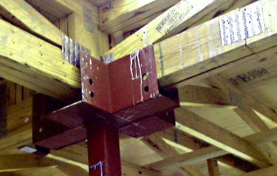 The multiple-membered wood-floor joists are designed to completely bear on the steel column