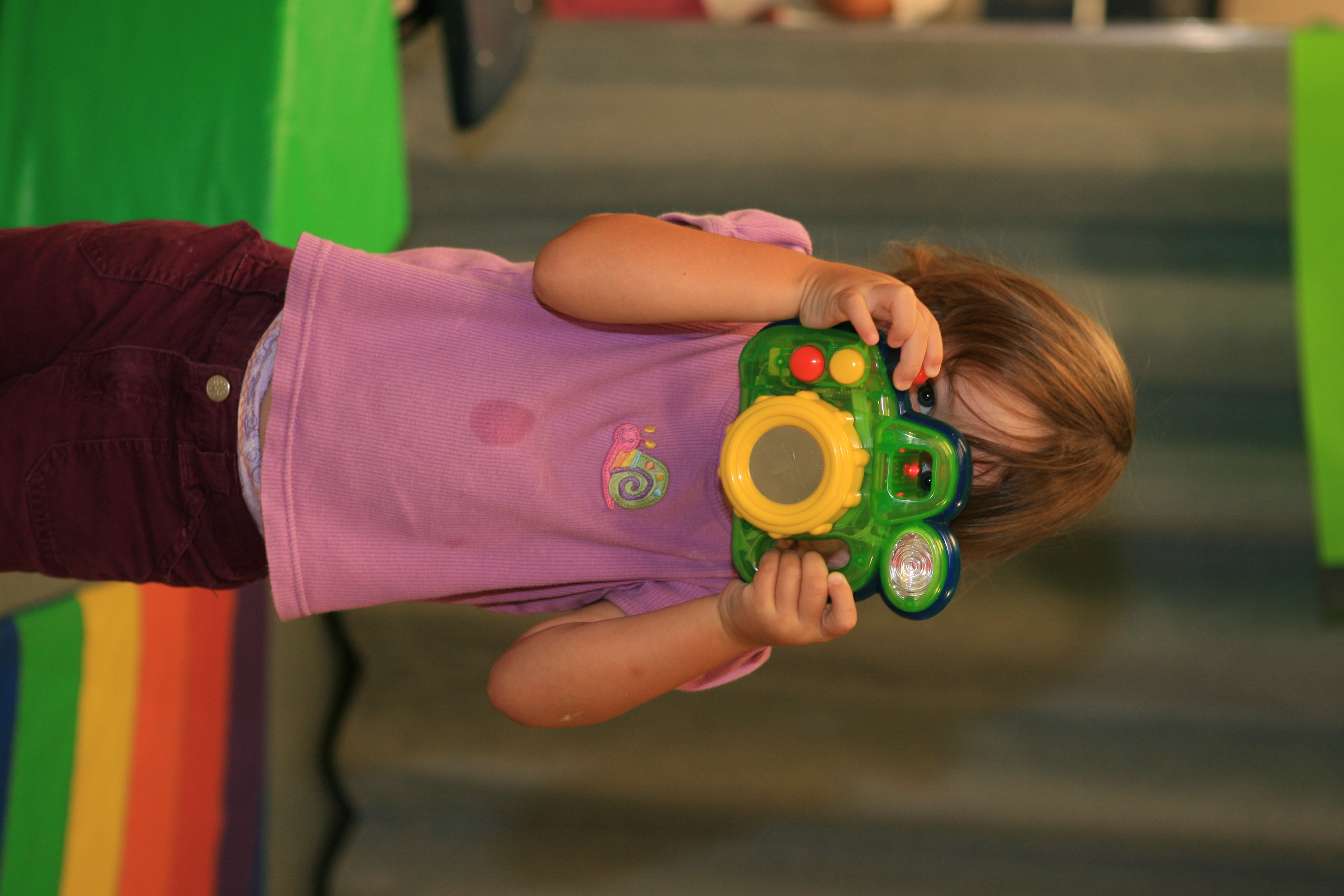 A little girl takes a picture using a toy camera