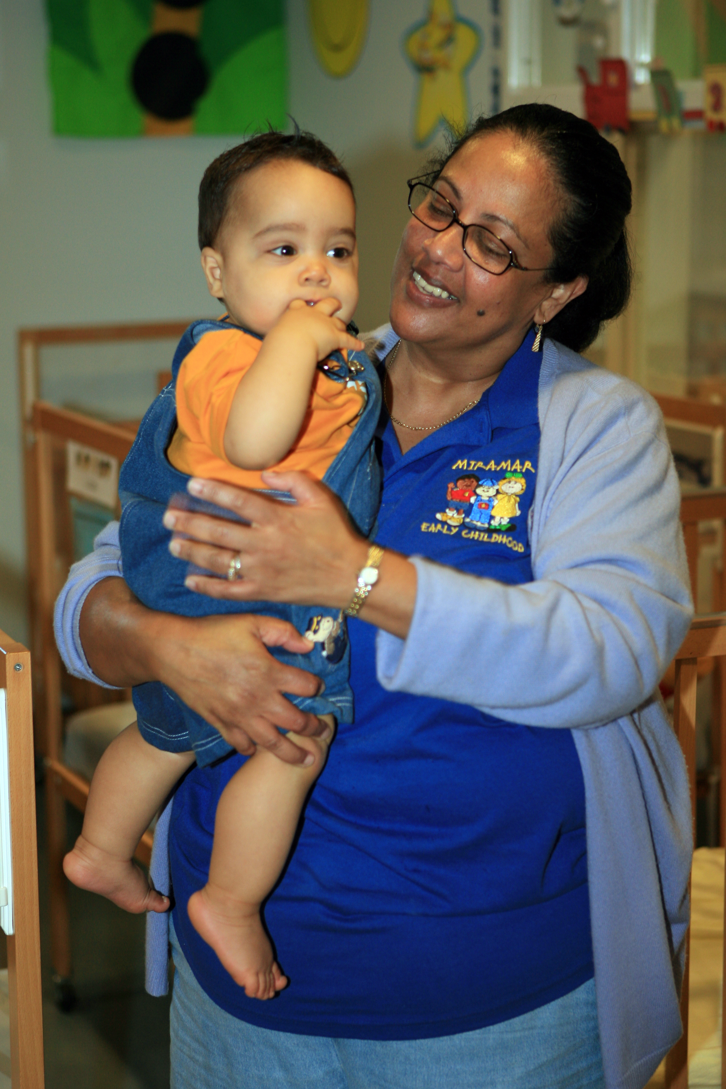An infant being held by a woman in an early childhood work shirt
