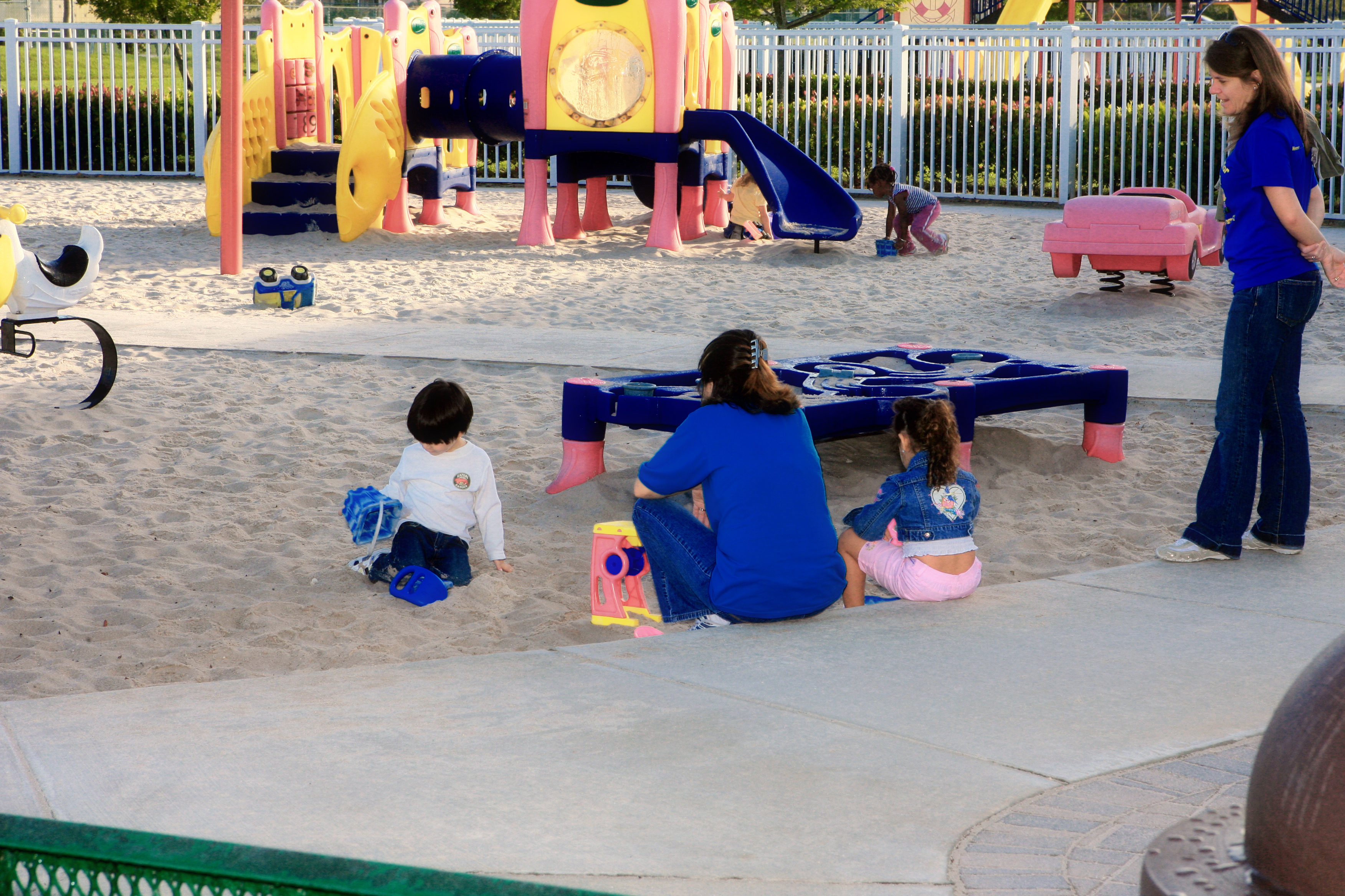 Kids playing in the sand on a playground while adults supervise