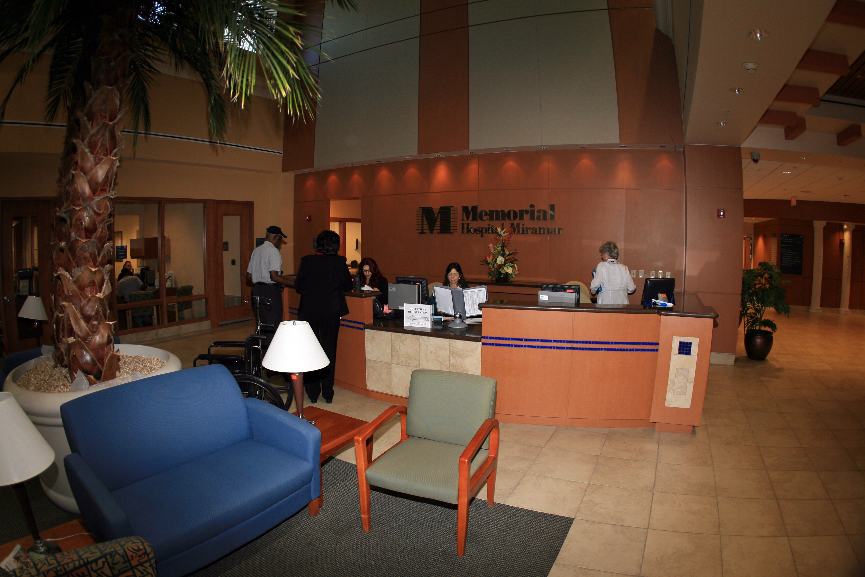 The lobby of the Memorial Hospital Miramar with people working at and standing around the front desk
