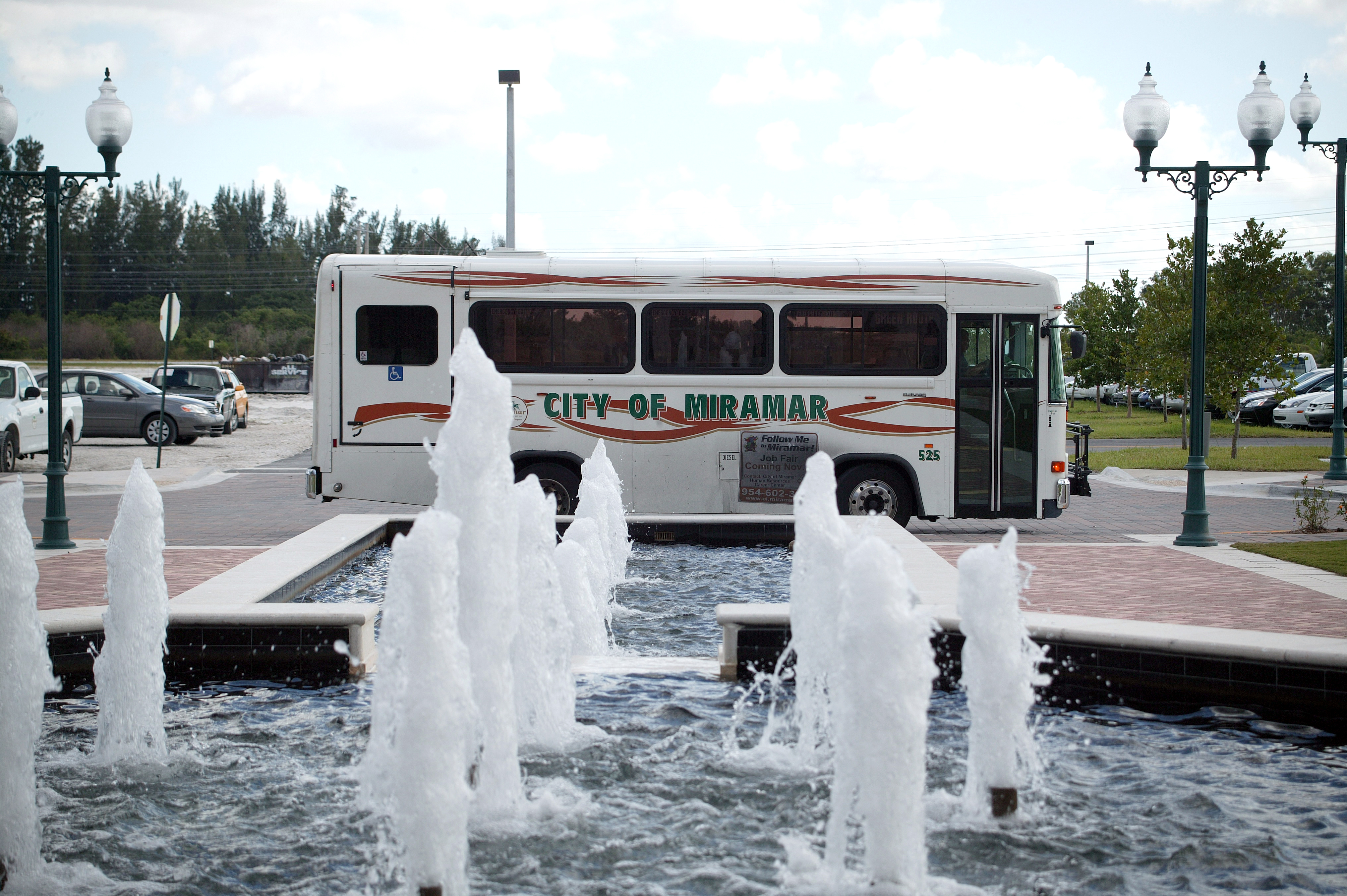 Public transportation bus with City of Miramar printed on the side behind fountains