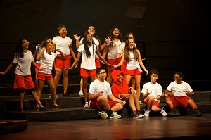 Group of kids on stage all wearing white shirts and red shorts