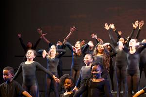 Group of kids in black unitards performing