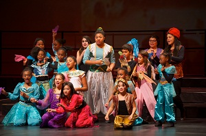 Group of kids putting on a stage performance in costume