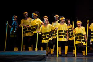 A group of kids on stage dressed in yellow brick shirts